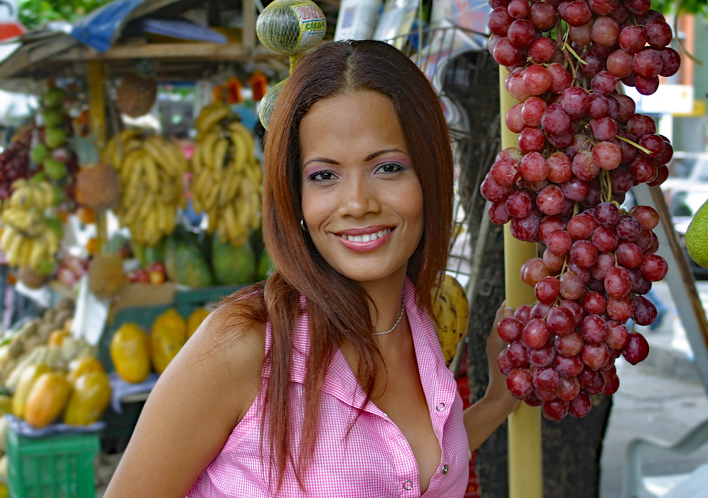 Colombian woman in front of a fruit stand