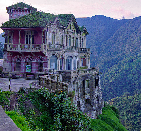 Old pink hotel with plants growing on the roof and the Andes in the background