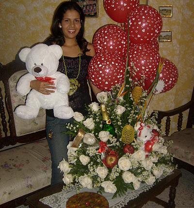 A Colombian woman receiving beautiful flowers, fruits, chocolate, cake, ballons, teddy bear and wine as a gift