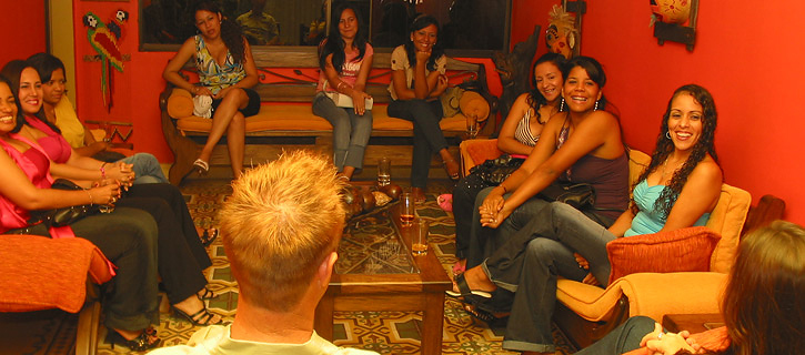 A group of Colombian women in a living room meeting a very happy man