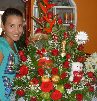 A Colombian woman receiving beautiful flowers, fruits, chocolate, teddy bear and wine as a gift