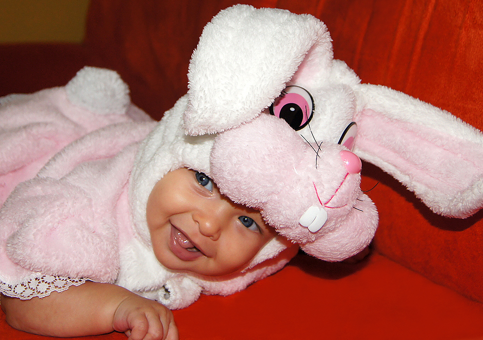 Smiling four month old American Colombian baby wearing her pink rabbit Halloween costume