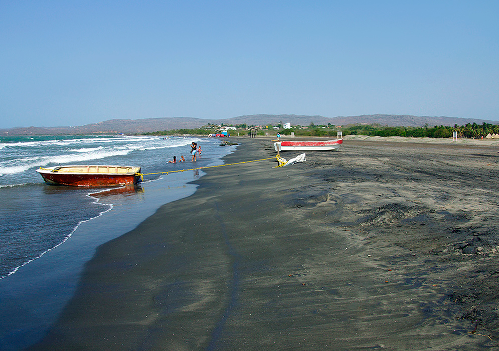 Two boats on the dark colored sands of Playa de Tubará