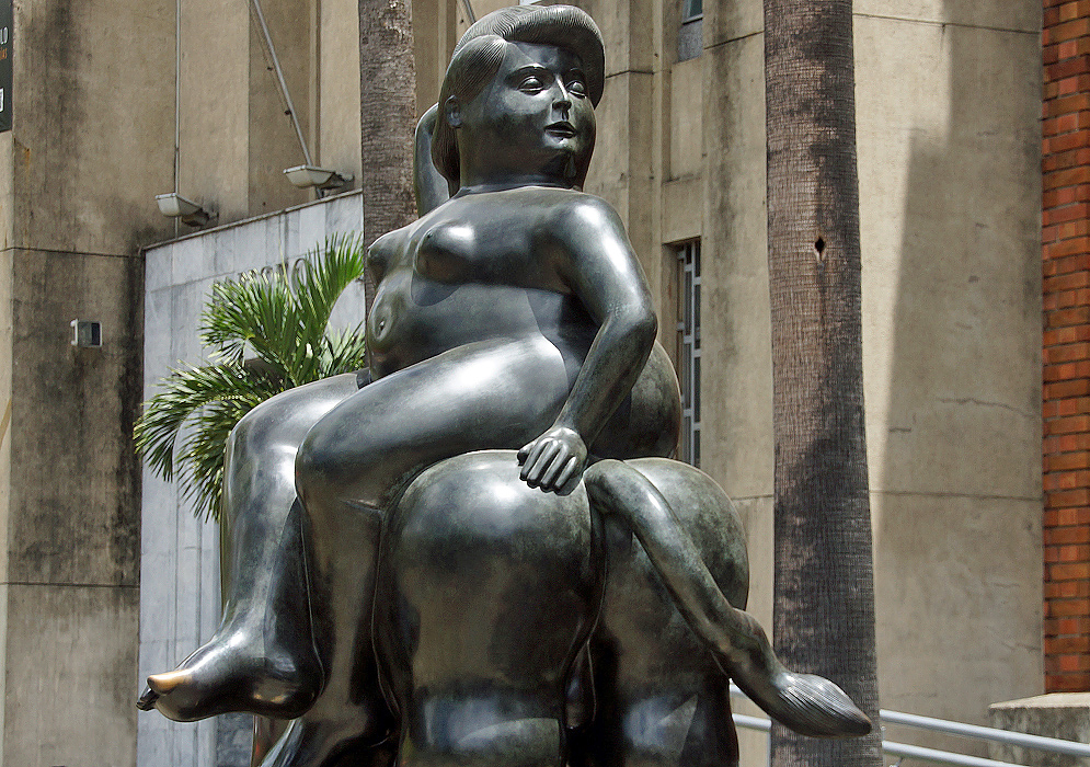A naked fat woman sitting side-saddle on a bull