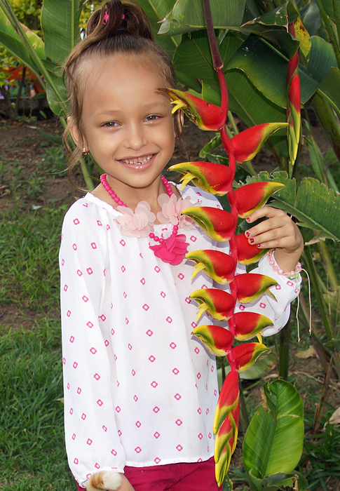 Happy little girl holding on to a long red and yellow Heliconia inflorescence