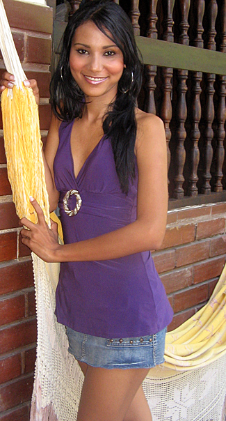 Slender morena Colombian Woman surrounded by flowers