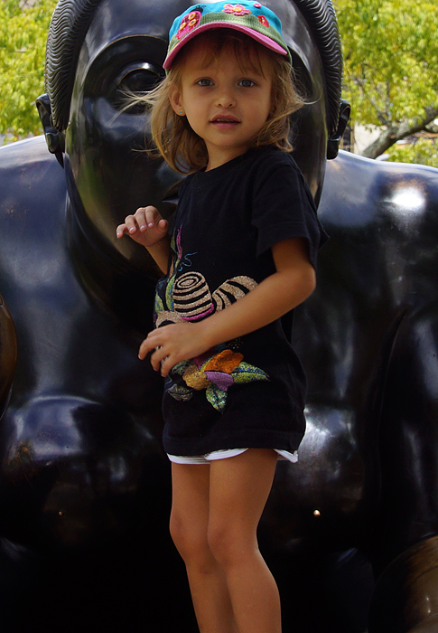 Little thin Colombian American girl standing in front of a Botero statue of a large woman