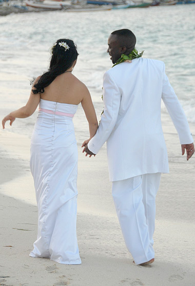 Sweethearts walking hand in hand on the beach after their wedding