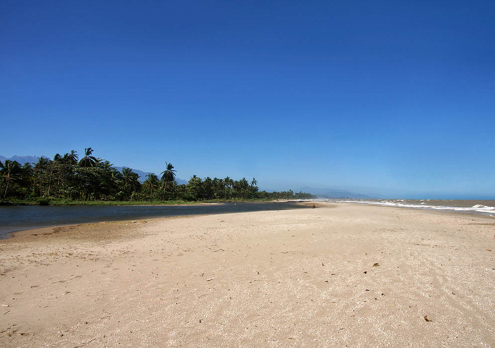 Large white beach with river, mountains and greenery and clear blue sky