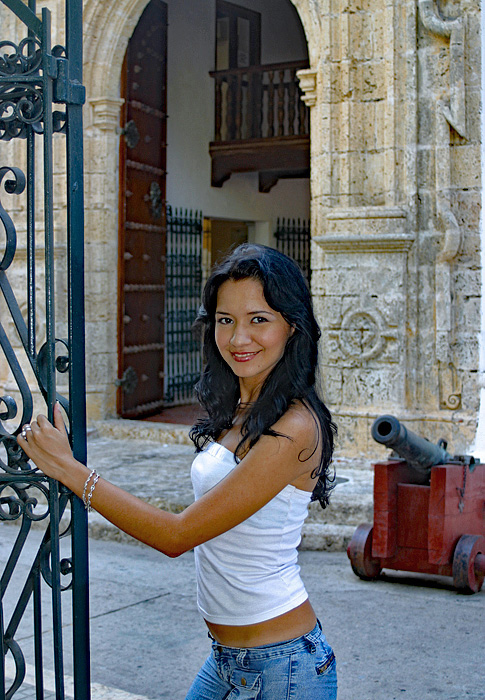 A Colombian woman in the Caribbean city of Cartagena in front of an old cannon