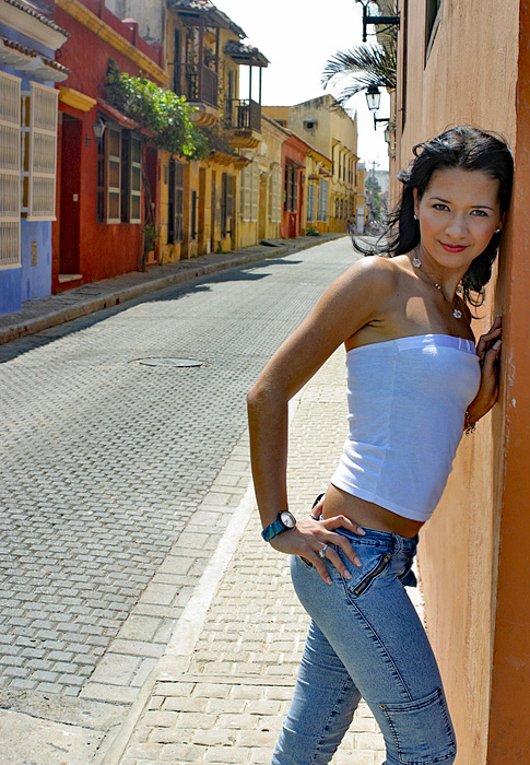 An exotic woman standing on a cobblestone street in Colonial Cartagena