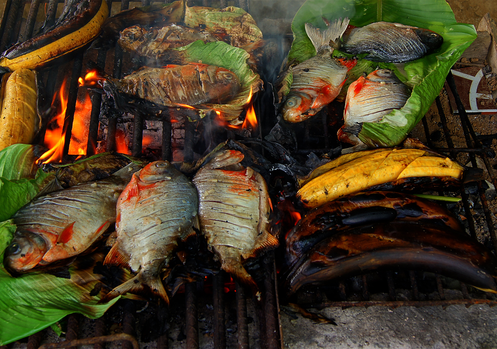 Cachama and yellow plantain cooking on a outdoor grill