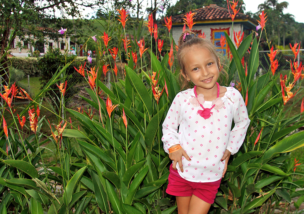 Pretty smiling blond five-year old wearing pink and white clothes in front of Heliconia psittacorum plants