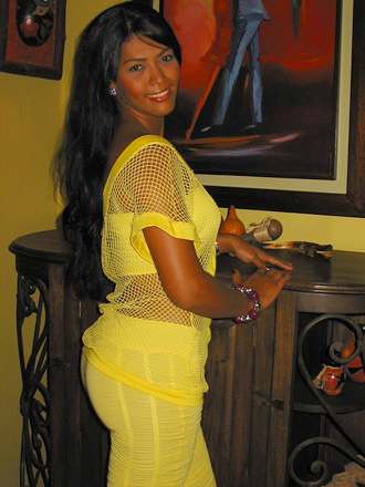 A well-built Colombian woman wearing yellow pants and fishnet shirt