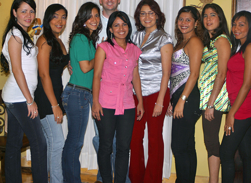 One man posing for a photo in the middle of eight South American women that he was introduced to