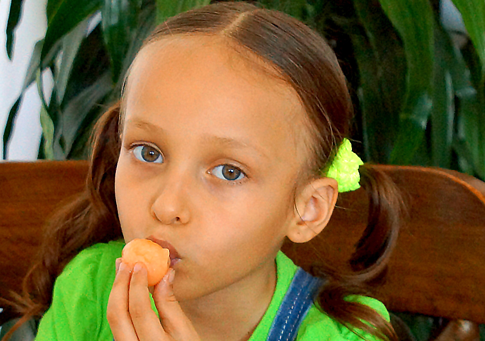 An attractive five-year old girl with an orange mamón near her mouth