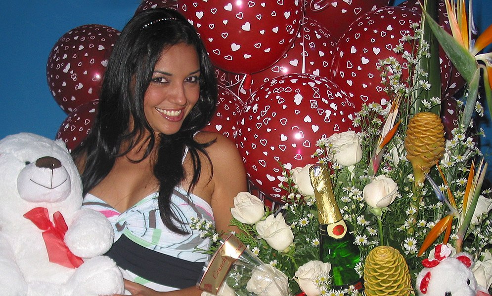 Dark hair, sexy Latin woman holding a white teddy bear and white roses with red ballons in the background