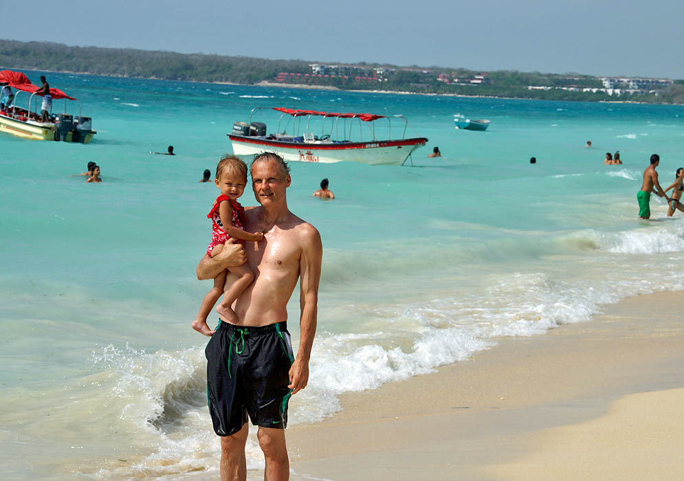 Father holding his two year old daughter on the seashore of Playa Blanca with blue water and boats in the background