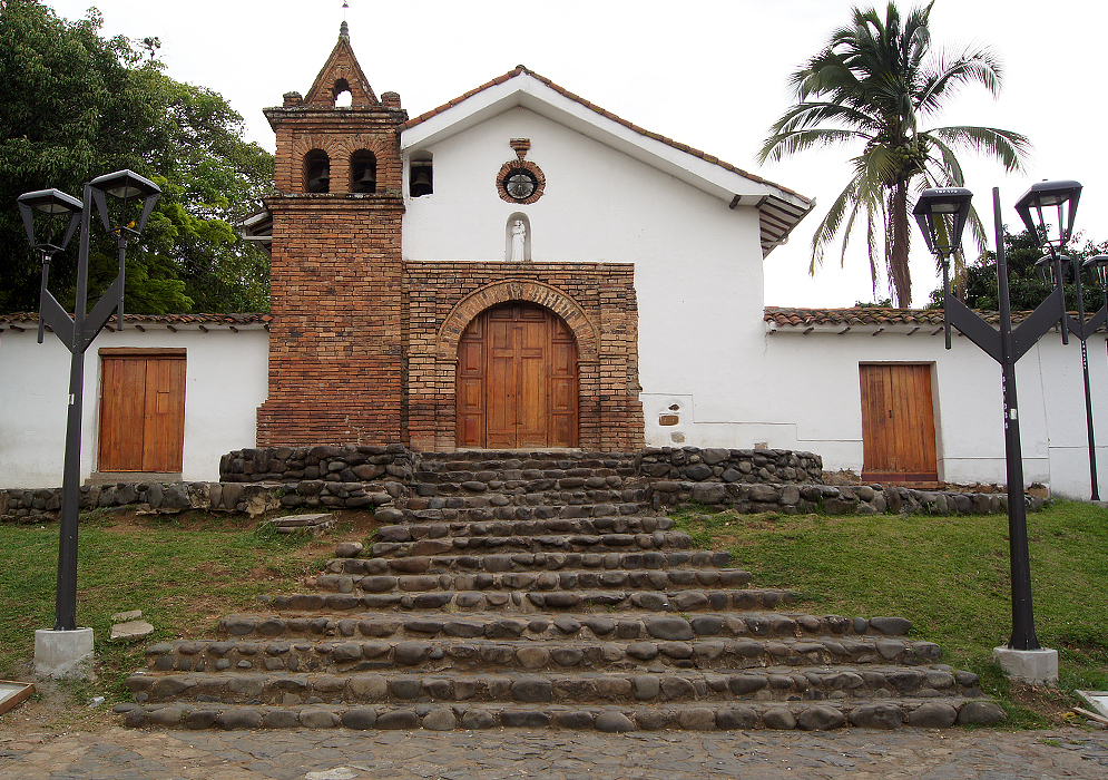 A small white church with bricks and stone steps