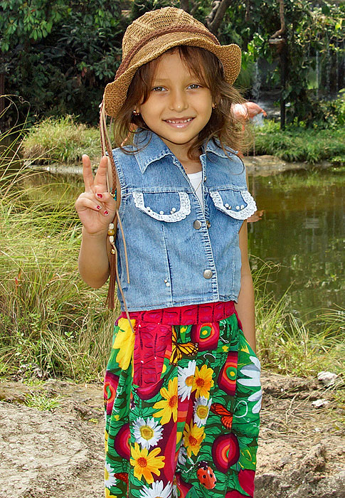 Stylish little girl wearing a jean vest, a brown hat and colorful pants give the peace sign
