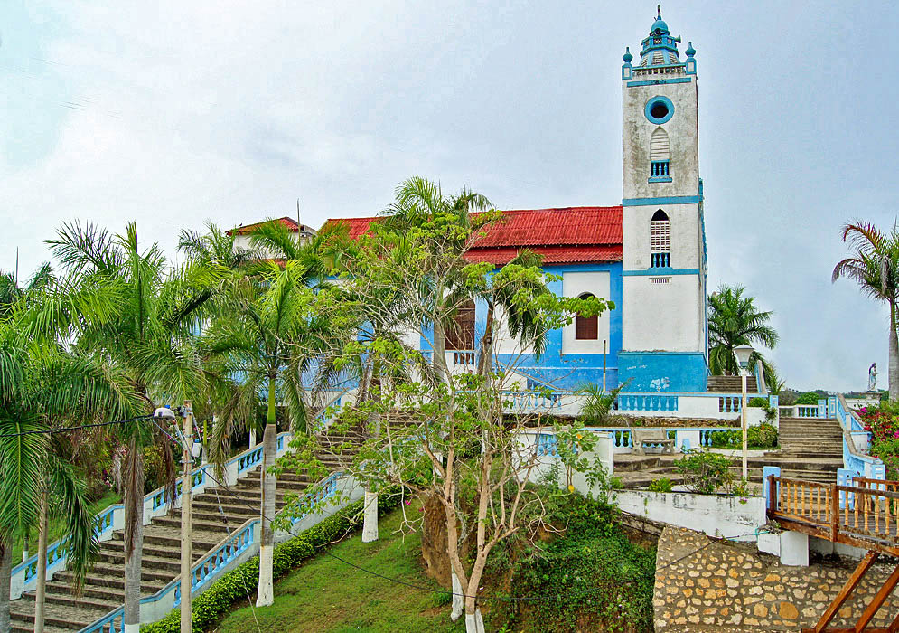 A blue and white church with a red roof  in Usiacuri, Colombia